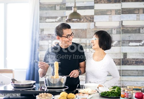 istock Chinese couple cooking at home 1149276782