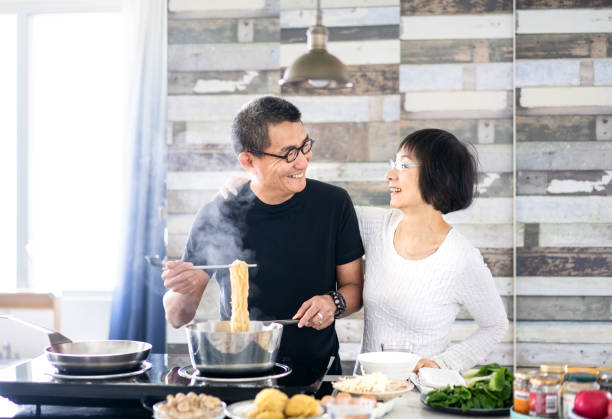 chinese couple cooking at home - cooker happy imagens e fotografias de stock