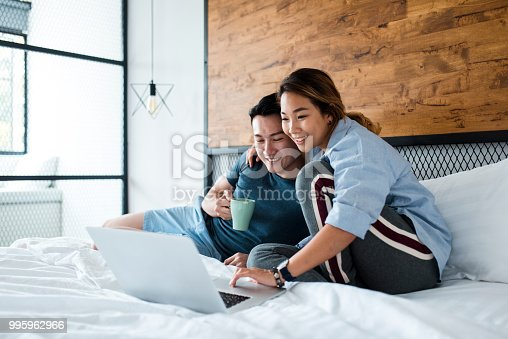 istock Chinese couple drinking coffee and using laptop in bed 995962966