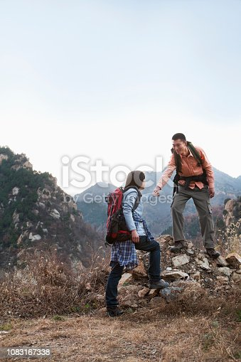 1083155024 istock photo Chinese couple hiking in rural landscape 1083167338