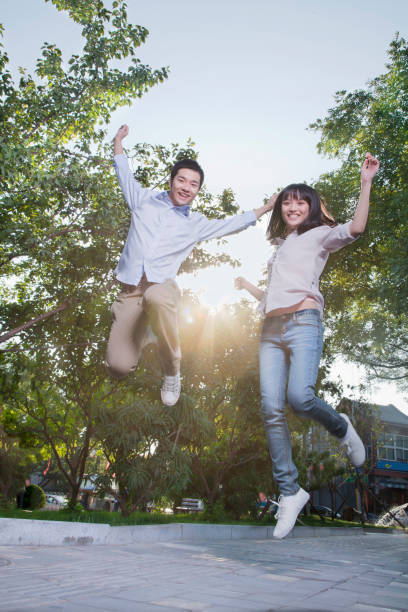chinese couple jumping in park - two students together asian foto e immagini stock
