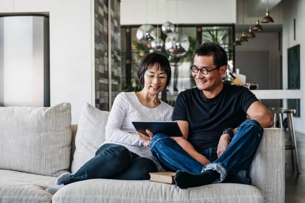 中國夫婦在沙發上看網上電影 - 亞洲 個照片及圖片檔
