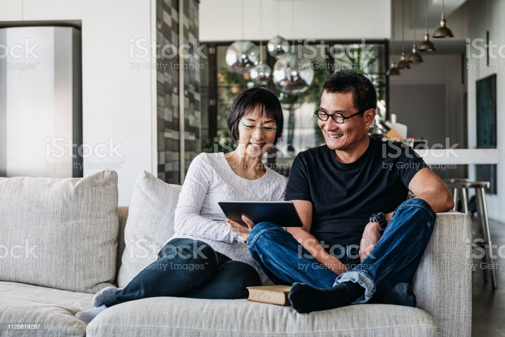 Chinese couple on sofa watching movie online stock photo