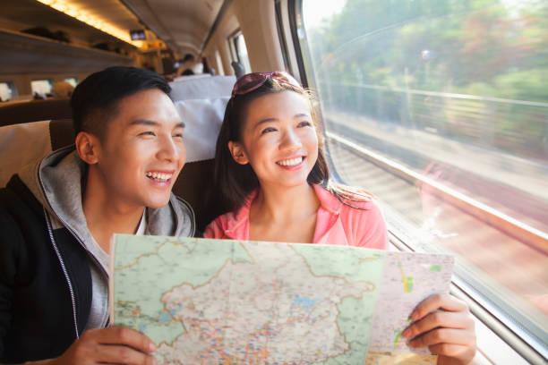 mapa de lectura de la pareja china en tren - viaje a asia fotografías e imágenes de stock