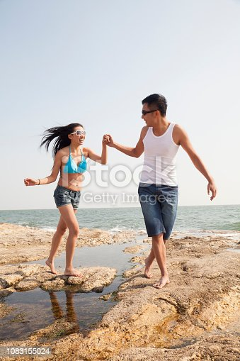 1083155024 istock photo Chinese couple running on beach 1083155024