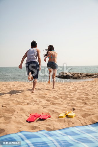1083155024 istock photo Chinese couple running on beach 1083155028