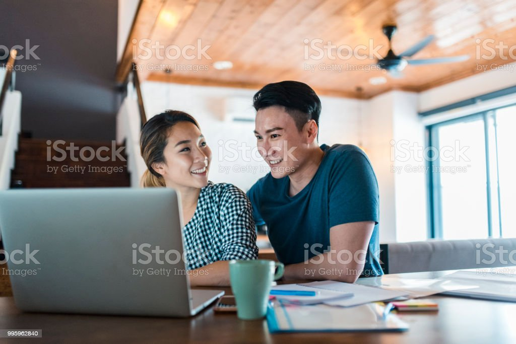 Chinese couple using a laptop in the living room and planning a vacation stock photo