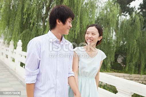 1083155024 istock photo Chinese couple walking in park 1083579406