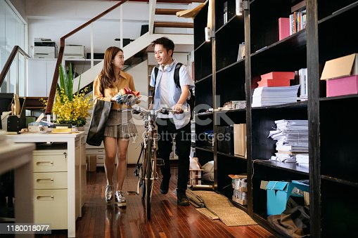 Young Chinese male bicycle commuter and female coworker with fabric samples arriving at Shanghai workplace in the morning and catching up.