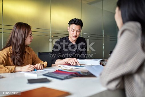 Young Asian male and female creatives sitting at conference table making color and fabric selections for a project.