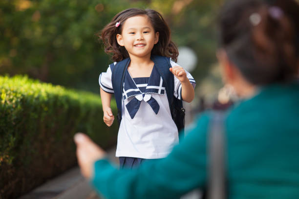 Chinese daughter running to greet her mother stock photo