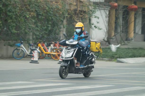 Chinesischer Liefermann trägt chirurgische Maske liefert Lebensmittel auf Elektrofahrrad – Foto