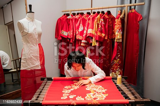 Focused male Chinese wedding dress designer stitching elaborate pattern with gold thread into fabric attached to embroidery frame.