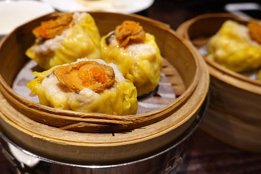 istock Chinese Dim Sum, Pork Meat Dumplings (Siu Mai) With Abalone in a bamboo basket 1194042433