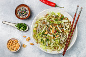 Chinese dish of starch glass noodles (rice, potatoes, beans) with meat (pork or beef), lettuce, cucumber, cucumbersoy sauce, ginger, sesame, cilantro, red pepper and roasted peanuts. Cold or hot salad. Eastern Asian cuisine