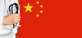 Chinese doctor holding a stethoscope in front of the Chinese Flag.