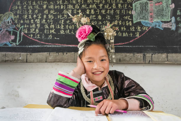 Chinese Dong People Girl sitting at teachers desk in school classroom stock photo