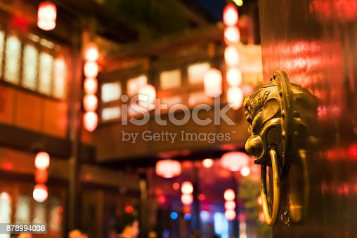 Chinese door knocker on a gate with chinese lanterns in the background