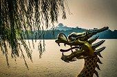 柳の木の下で湖と遠くの中国建築背景の中国のドラゴン