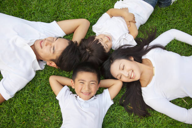 Chinese family laying in grass stock photo