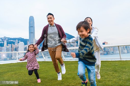 Carefree young Chinese family holding hands and racing on grass at Ocean Terminal Deck in Hong Kong.