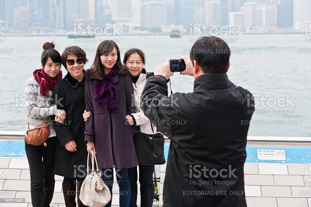 Chinese family tourists taking photo Hong Kong Harbor royalty-free stock photo