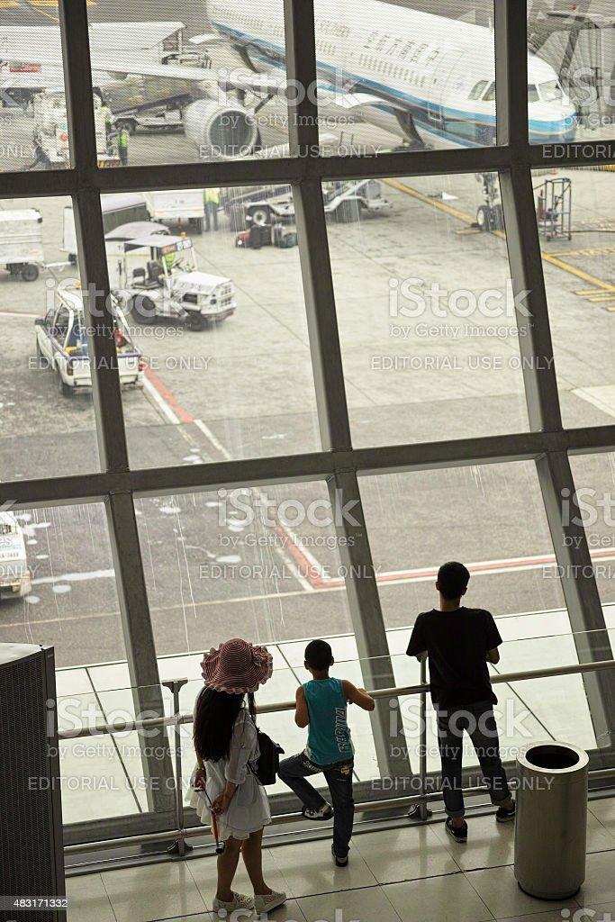 Chinese family waiting to depart at Suvarnabhumi Airport. stock photo