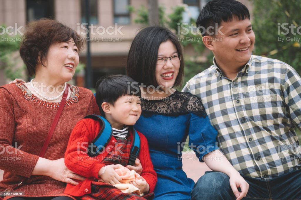 chinese family with grandmother sitting outdoors stock photo