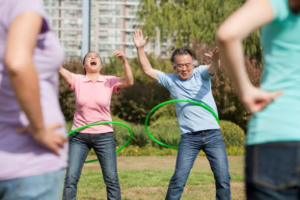 chinesische familie mit kunststoff hoop im park - hula hoop workout stock-fotos und bilder