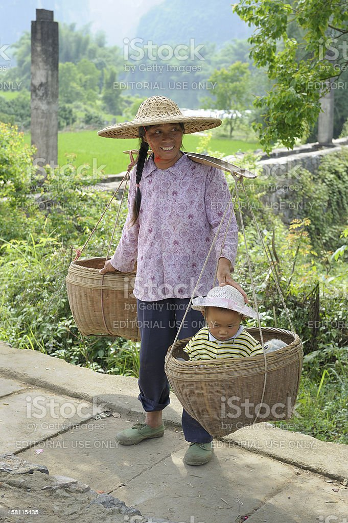 Chinese farmer with child in basket stock photo