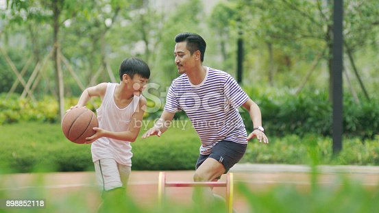 istock Chinese father & son playing basketball in garden in morning 898852118