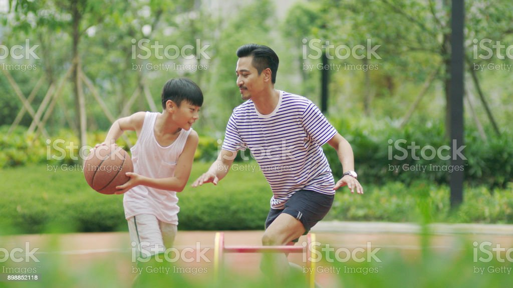 Chinese father & son playing basketball in garden in morning stock photo