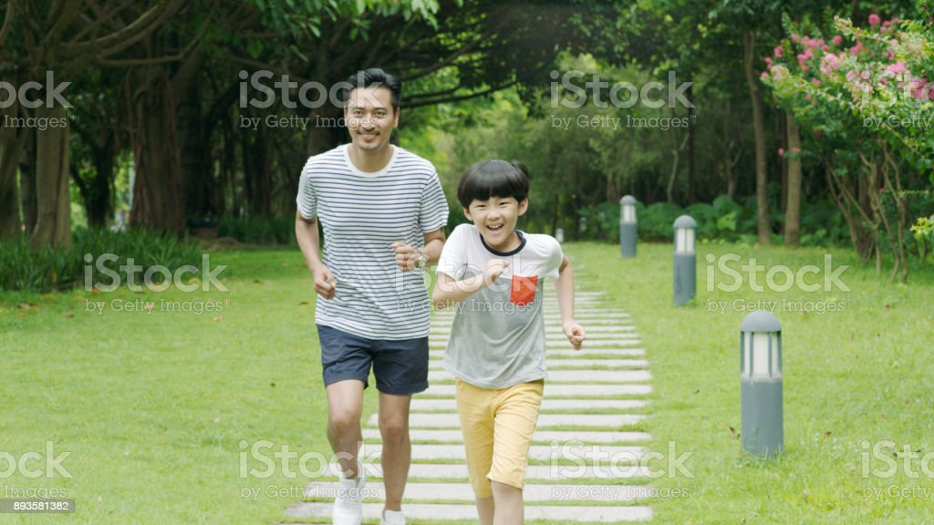 Chinese father & son smiling & running in park in summer stock photo