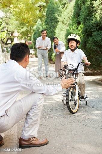 Chinese father watching son ride bicycle