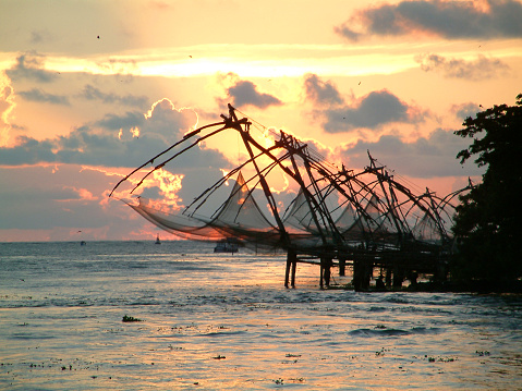 A Chinese fishing net and a small hut with coconut trees under a blue and white cloudy sky, River photography with a Chinese fishing net from Kerala, India