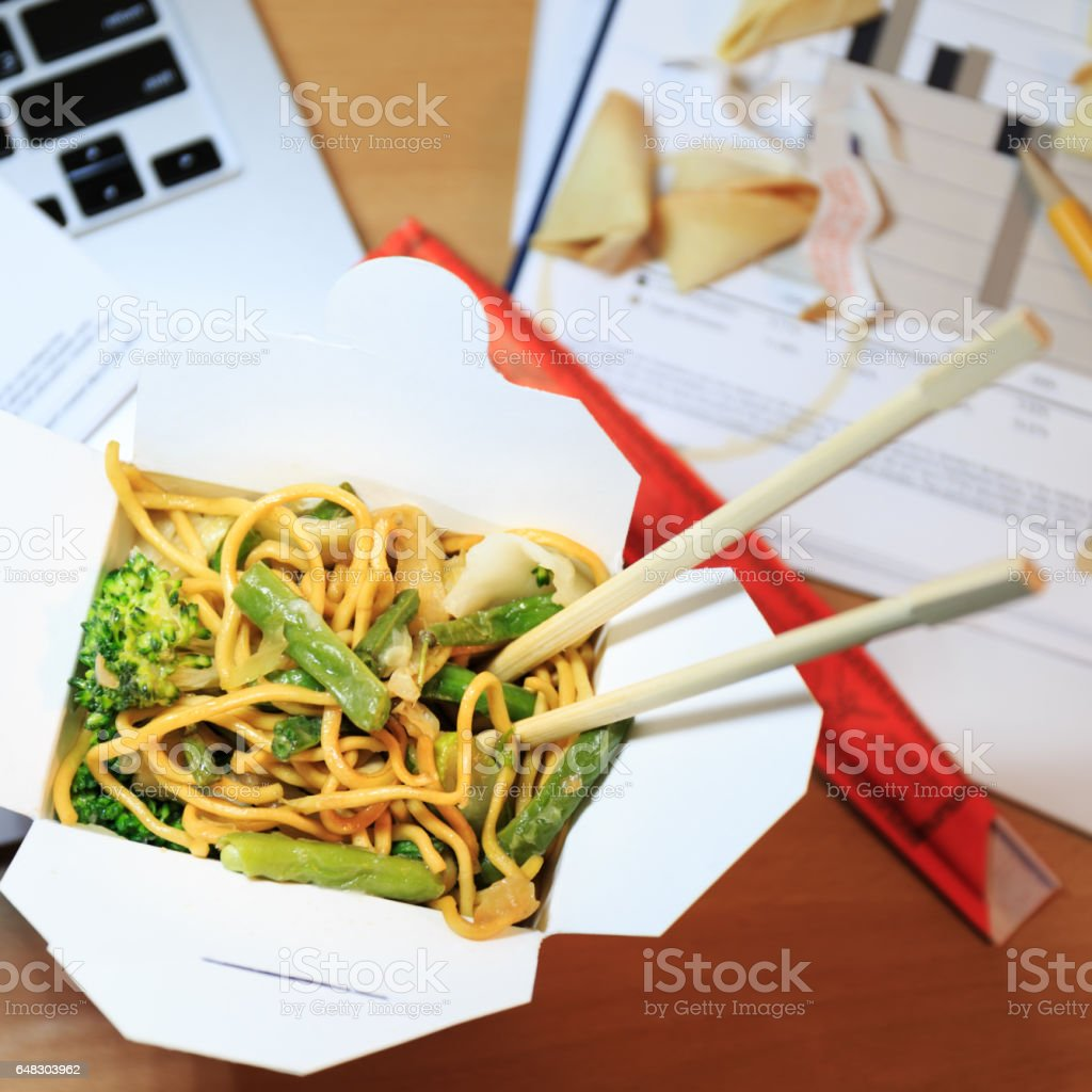 Chinese food box on the office desk. Eating at the office. Overtime...