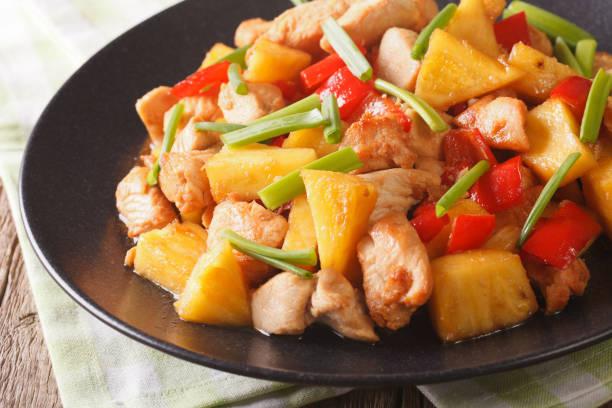 chinesisches essen: gebratenes hähnchen mit ananas in süß-saurer soße nahaufnahme. horizontale - ananas huhn salate stock-fotos und bilder