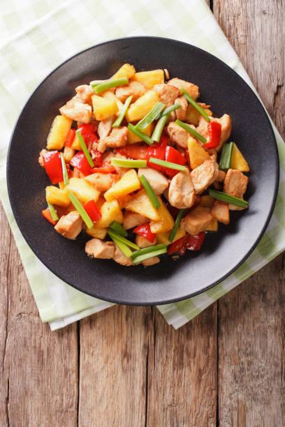 chinesisches essen: gebratenes hähnchen mit ananas in süß-saurer soße nahaufnahme. vertikale ansicht von oben - ananas huhn salate stock-fotos und bilder