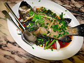 A traditional Chinese cuisine. Steamed whole fish top with ginger and scallion in soy sauce.