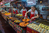 Beijing, China - 27th September 2013: Young cooks preparing and serving delicious street food at a night market in the Wangfujing district in the heart of Beijing, China's vibrant capital city.