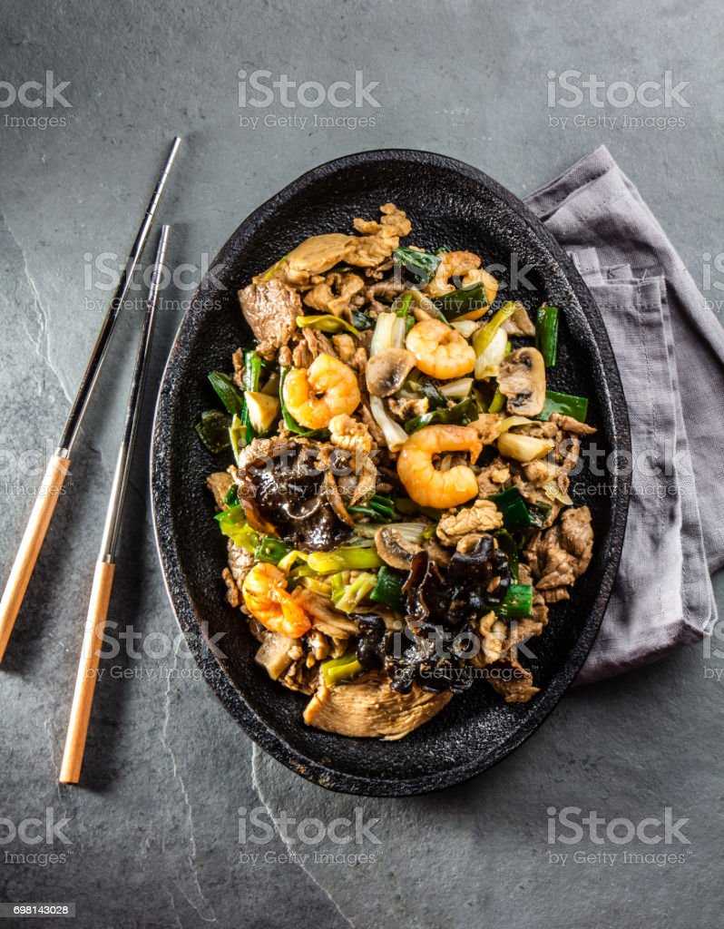 Chinese food. Te pam sao. Pan of fried beef, pork, chicken, shrimps, shiitake mushroom, champions and spring onion.  served with rice on gray slate background. stock photo