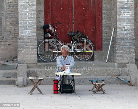 istock Chinese fortune teller sitting at the entrance to a Buddhist monastery, Inner Mongolia 858024128