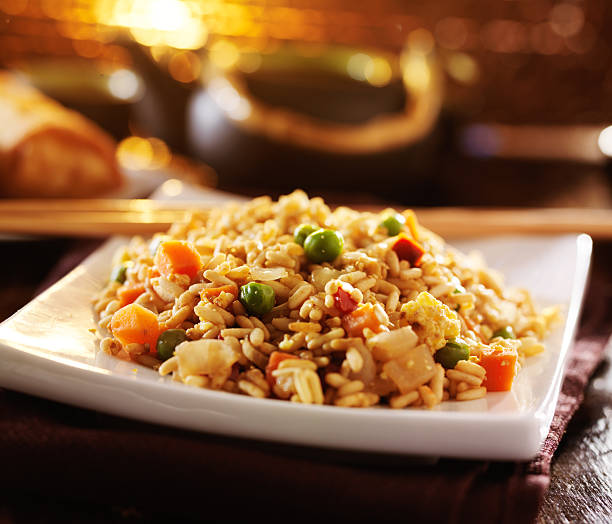 chinese fried rice on plate with orange glow chinese fried rice on plate with orange glow in background fried rice stock pictures, royalty-free photos & images
