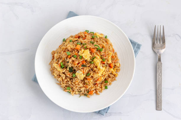 Chinese Fried Rice with Vegetable and Egg Chinese / Asian Egg and Vegetable Fried Rice on a White Plate on the White Background Directly Above Photo. fried rice stock pictures, royalty-free photos & images