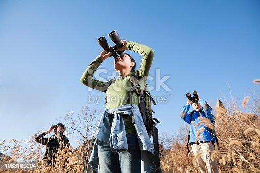 Chinese friends using binoculars in rural landscape