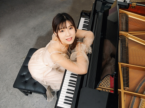 Chinese girl and grand piano. Beautiful young girl pianist.