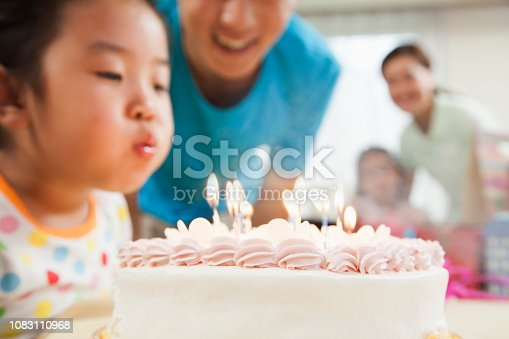 Chinese girl blowing out candles on birthday cake