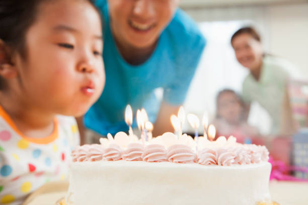 Chinese girl blowing out candles on birthday cake stock photo
