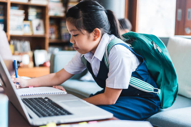 chinese girl doing homework and using laptop - girl study home laptop front imagens e fotografias de stock