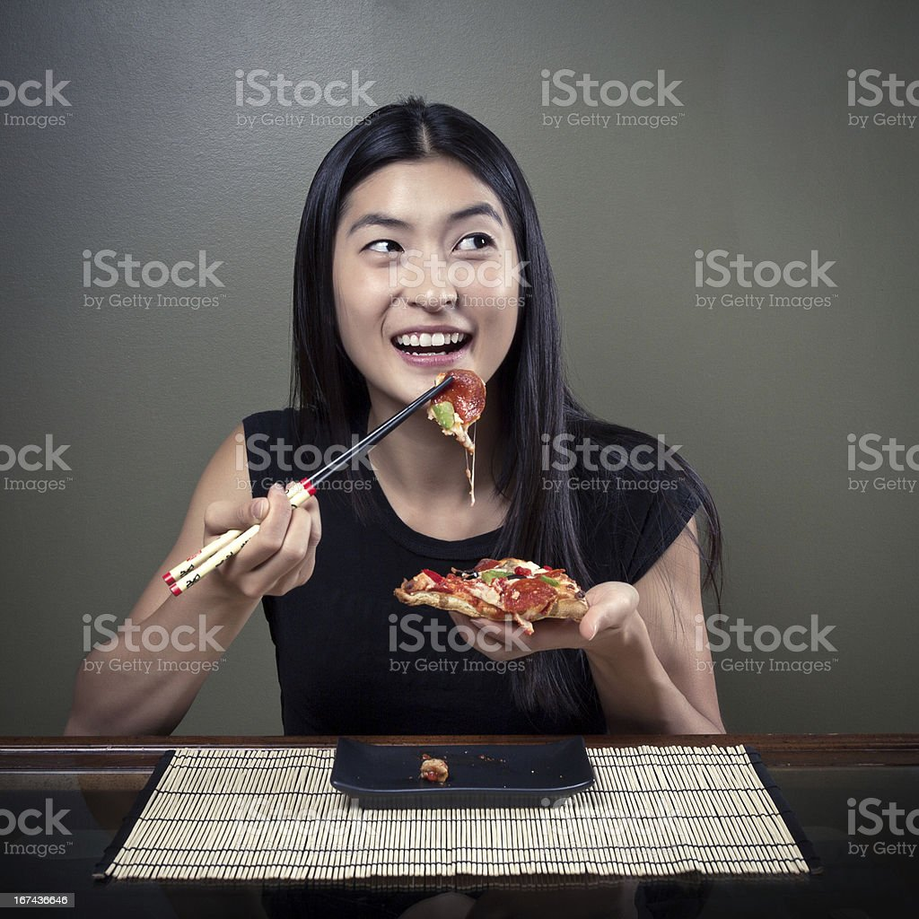 Chinese Girl Eating Pizza With Chopsticks royalty-free stock photo